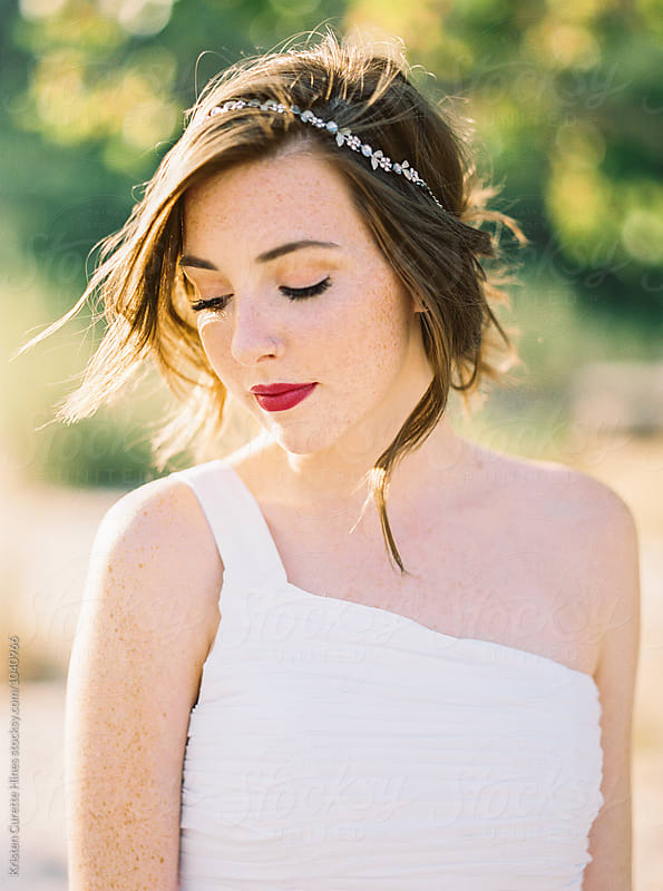 Portrait of a woman with freckles wearing a white dress / outdoors by Kristen Curette Hines for Stocksy United