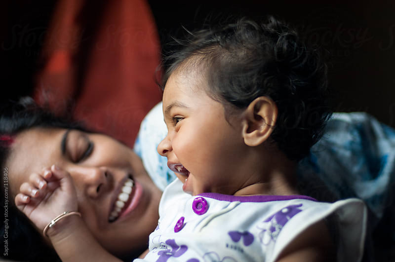 Baby girl sharing cheerful moment with her mother by Saptak Ganguly for Stocksy United