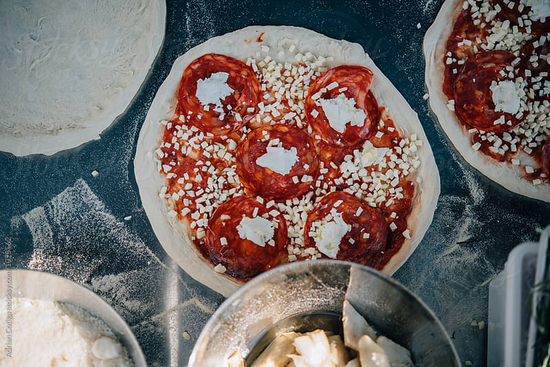 Pizza prepared for cooking by Adrian Cotiga for Stocksy United