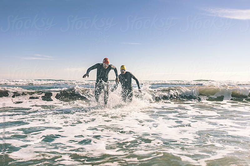 Two triathletes leaving the water on triathlon race. by BONNINSTUDIO for Stocksy United