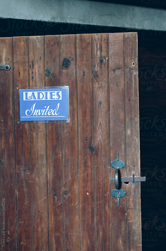 SIgnpost 'ladies invited' on wooden door by Trent Lanz for Stocksy United