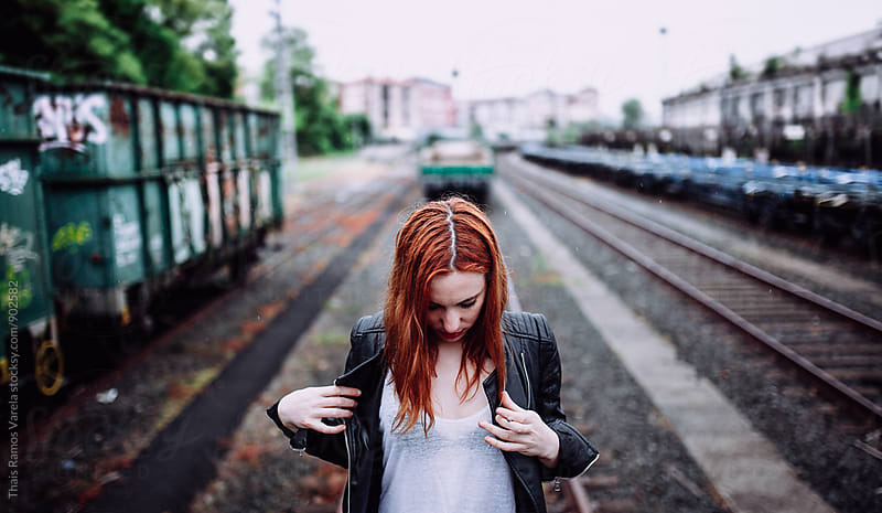 ginger woman on a railway by Thais Ramos Varela for Stocksy United