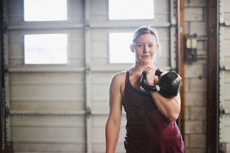 Young, active woman holding kettlebell in gym by Rob and Julia Campbell for Stocksy United