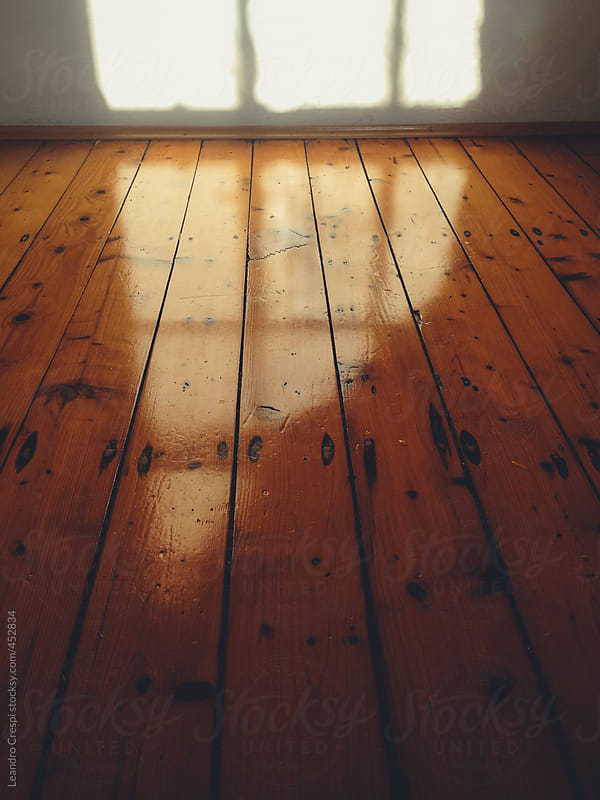 Window light reflected on a timber floor by Leandro Crespi for Stocksy United