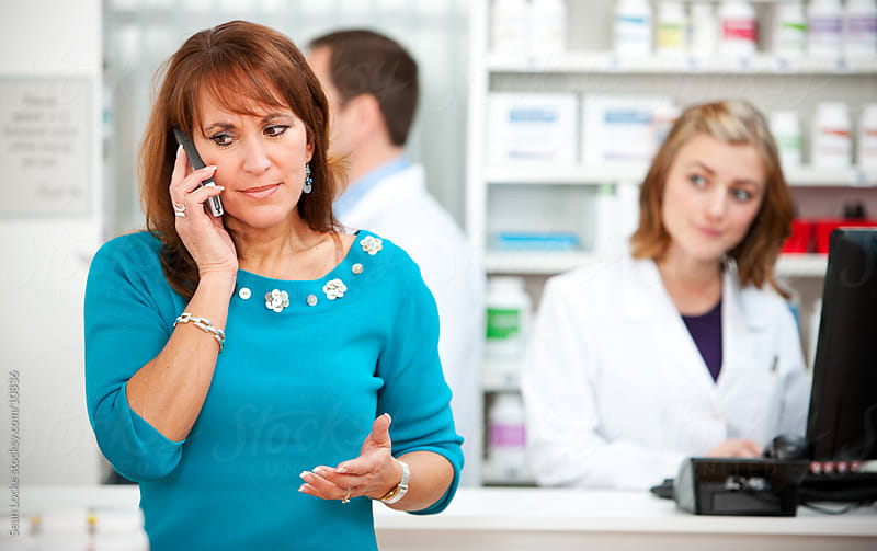 Pharmacy: Woman Customer on Phone with Doctor by Sean Locke for Stocksy United