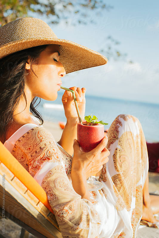 Pretty Exotic Beauty Drinking Strawberry Smoothie on Beach Sunbed by VISUALSPECTRUM for Stocksy United