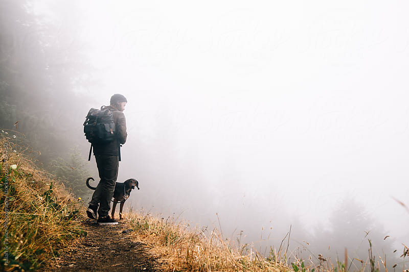 Man with his dog on a trail by Isaiah & Taylor Photography for Stocksy United
