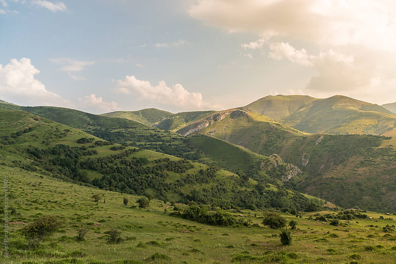 Landscape of green meadows with a blue sky by Javier Pardina for Stocksy United