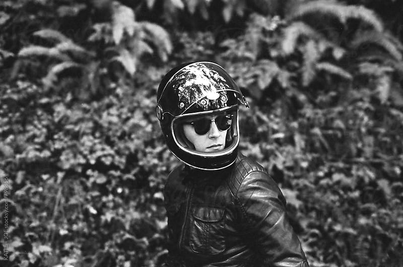 black and white photo of a man wearing a motorcycle helmet and sunglasses by KATIE + JOE for Stocksy United