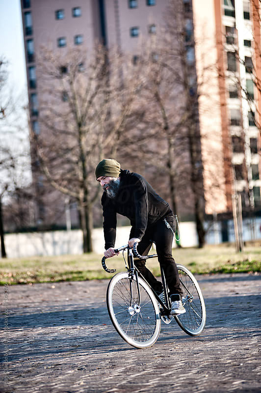 Hipster man ride his fixed gear bike in a suburb of Milano by Jean-Claude Manfredi for Stocksy United