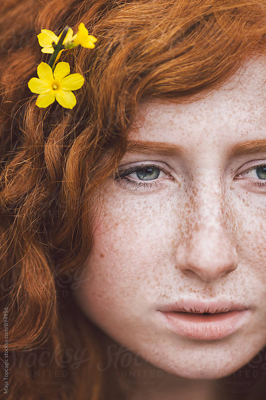 Portrait of a redhead with freckles by Maja Topcagic for Stocksy United