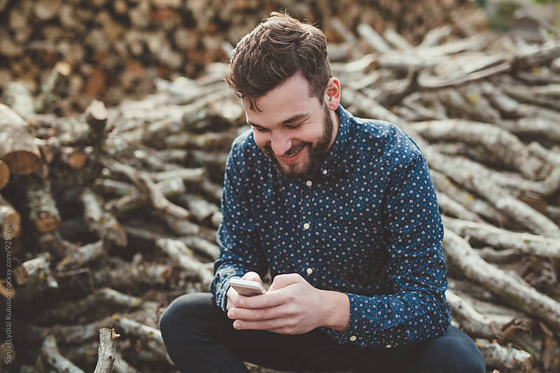 Handsome beardy hipster guy texting and smiling by Sanja (Lydia) Kulušić for Stocksy United