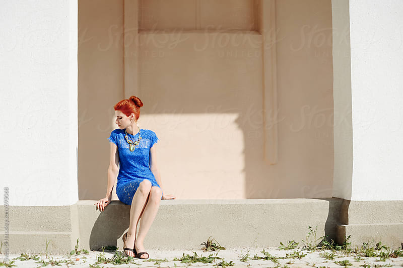 Red-haired girl in a blue dress by Svetlana Shchemeleva for Stocksy United