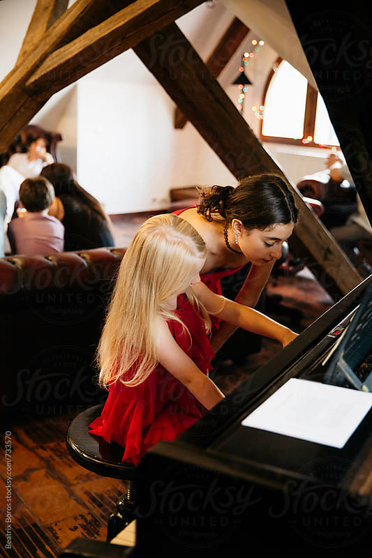 Blond little girl playing the piano and her sister helps her by Beatrix Boros for Stocksy United