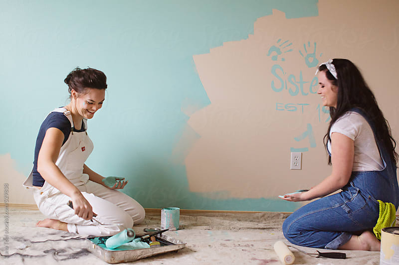 Sisters paint a wall together by Tana Teel for Stocksy United