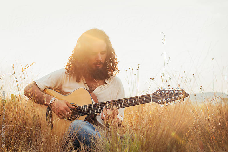 Bearded Young Man With Long Hair Playing Guitar in Field by VISUALSPECTRUM for Stocksy United