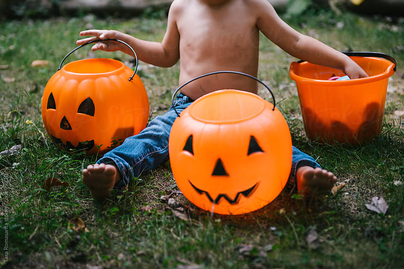 toddler reaches into halloween pumpkin decorations by Tara Romasanta for Stocksy United