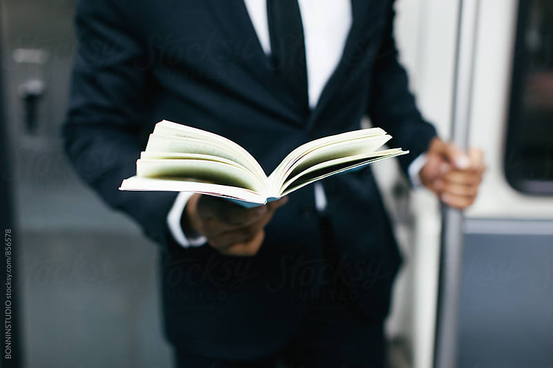 Closeup of a businessman reading a book on subway. by BONNINSTUDIO for Stocksy United