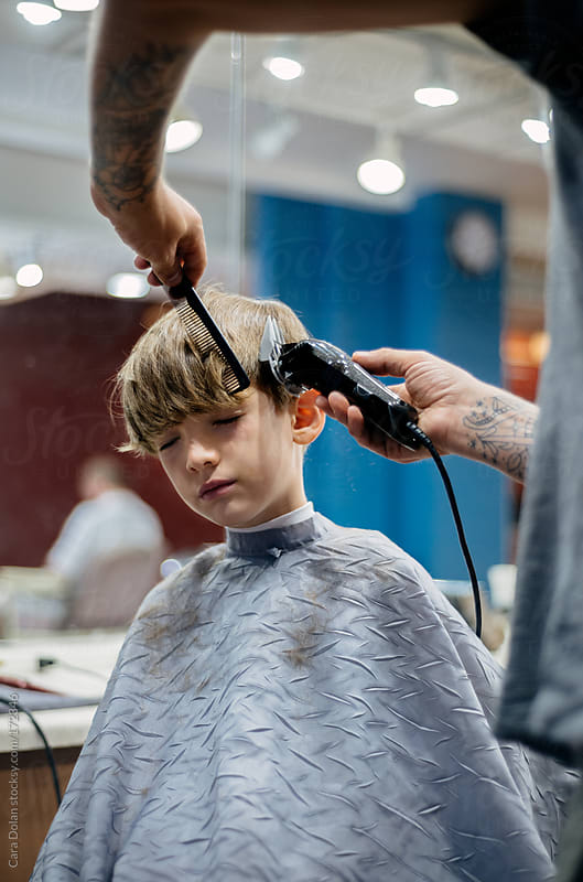 Boy gets a haircut at a barber shop by Cara Dolan for Stocksy United