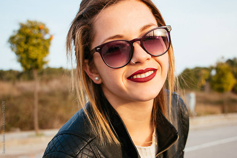 Portrait of young woman with sunglasses smiling by Susana Ramírez for Stocksy United