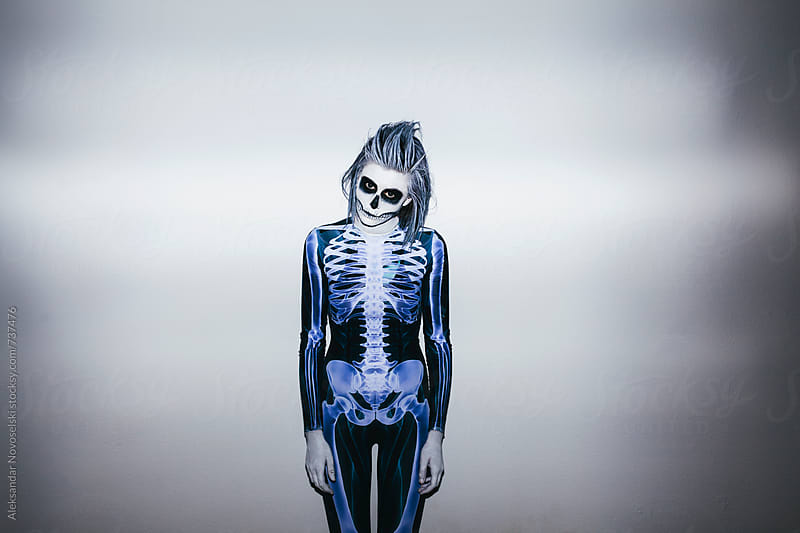 Young woman with skeleton costume and halloween make up against white wall by Aleksandar Novoselski for Stocksy United