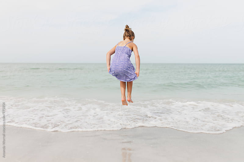 Girl jumping in the gentle ocean waves by Amanda Worrall for Stocksy United