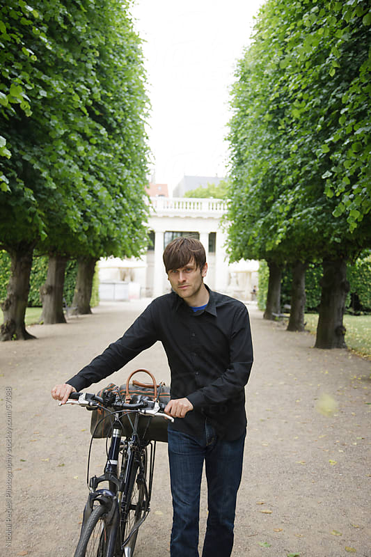 Man with bike in a park by Nicolai Perjesi Photography for Stocksy United