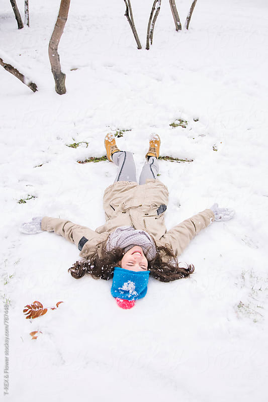 Young brunette making snow angel  by Danil Nevsky for Stocksy United