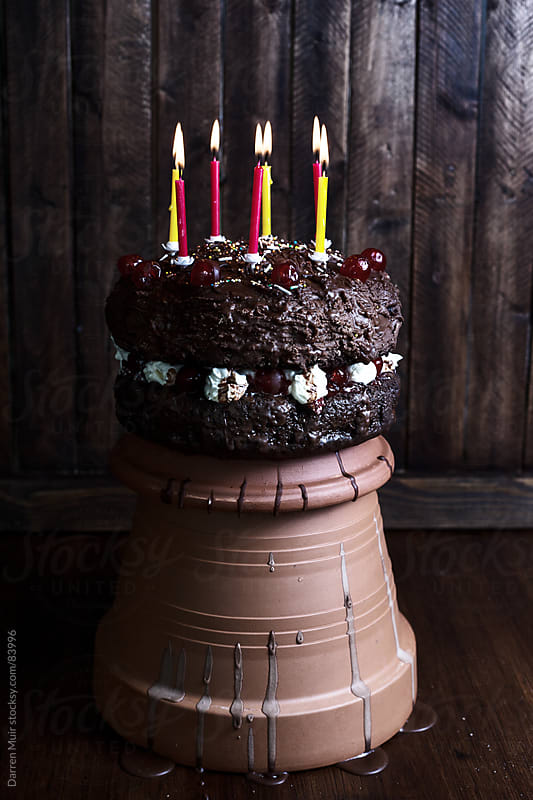 Chocolate cake with candles.  by Darren Muir for Stocksy United