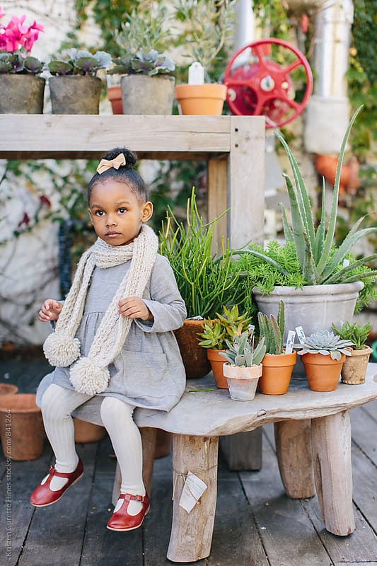 A little girl sitting on a stool in a garden / flower market.  by Kristen Curette Hines for Stocksy United