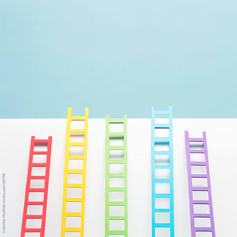 Rainbow ladders leaning on white wall... by Catherine MacBride for Stocksy United