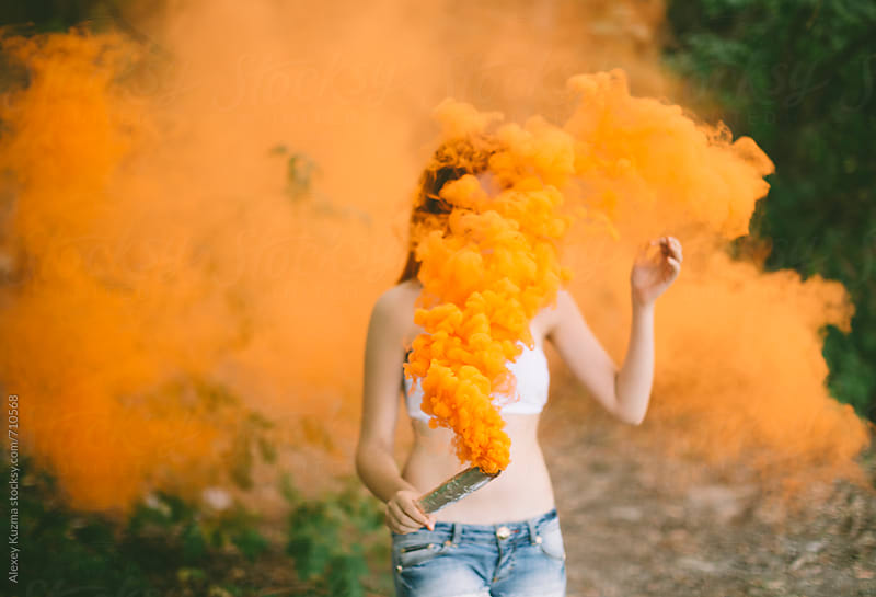woman with orange smoke bomb at nature .  by Alexey Kuzma for Stocksy United