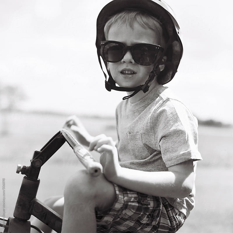 boy riding his tricycle in black and white square  by Meghan Boyer for Stocksy United