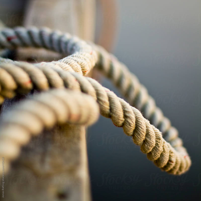 Rope hanging out of the jetty by Jonas Räfling for Stocksy United
