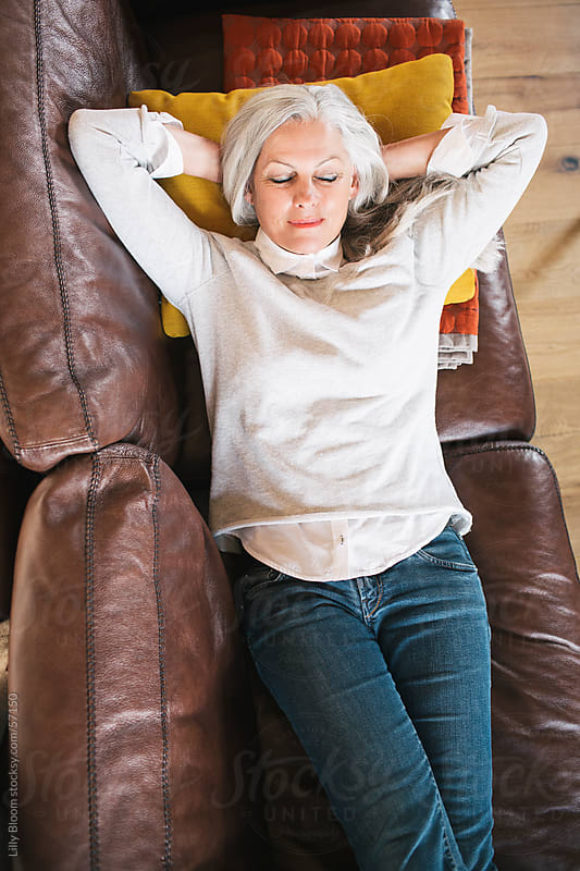Senior woman resting on her sofa by Lilly Bloom for Stocksy United