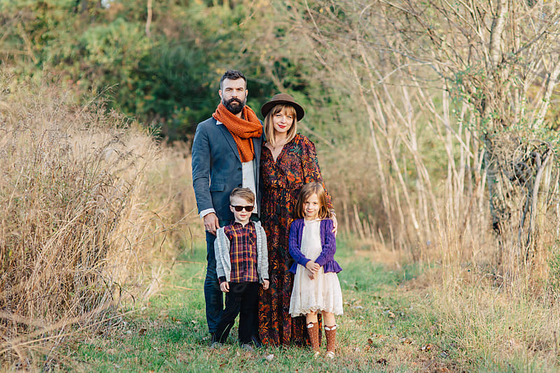 Beautiful and trendy family standing by a field by Jakob for Stocksy United