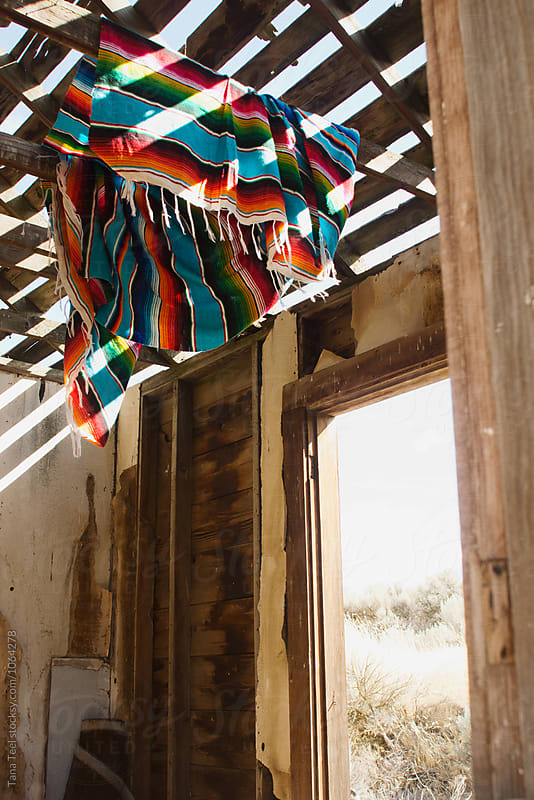 Mexican serape blanket hangs from open rafters of  shack by Tana Teel for Stocksy United
