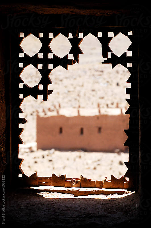 Views from a broken window os a fortified mudbrick kasbah in the Draa Valley, Morocco by Bisual Studio for Stocksy United