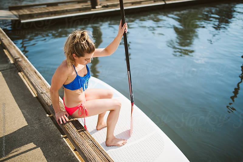 Young blonde fit woman on a dock with paddle board. by Kate Daigneault for Stocksy United