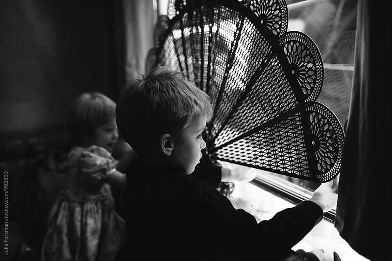 Two children look out of a window covered with an old fashioned screen. by Julia Forsman for Stocksy United
