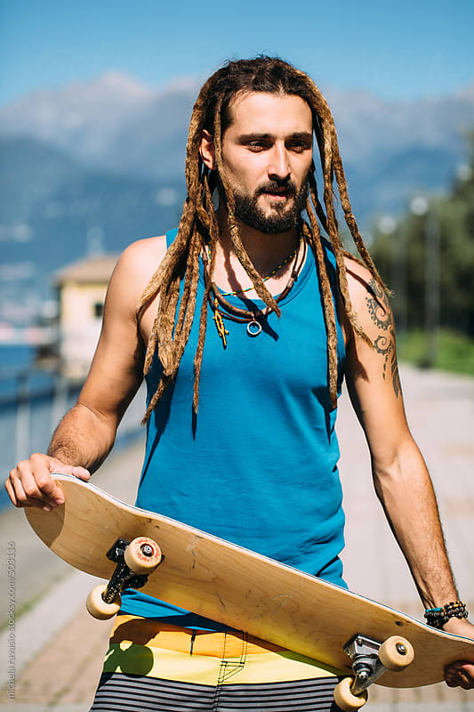 Boy with dreadlock holding his skateboard by michela ravasio for Stocksy United