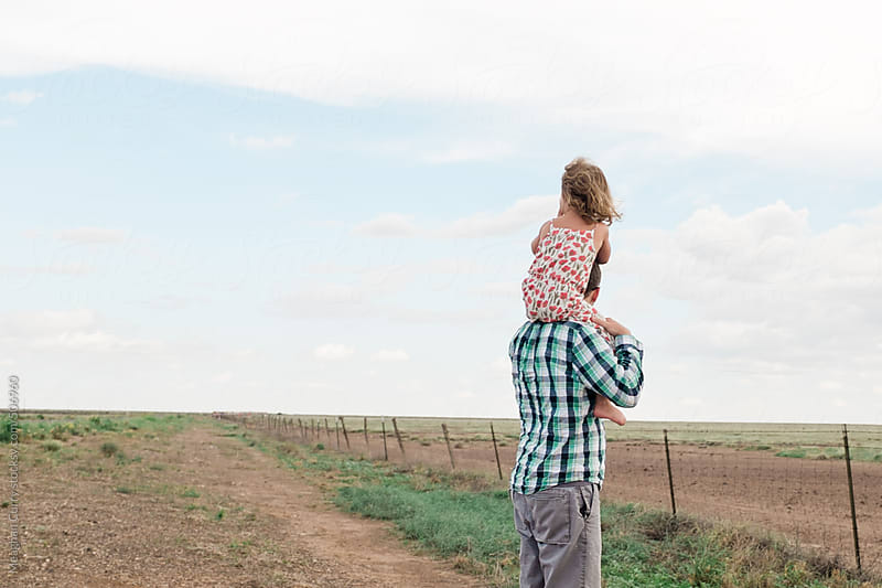little girl sitting on her father's shoulders looking out over a field by Meaghan Curry for Stocksy United