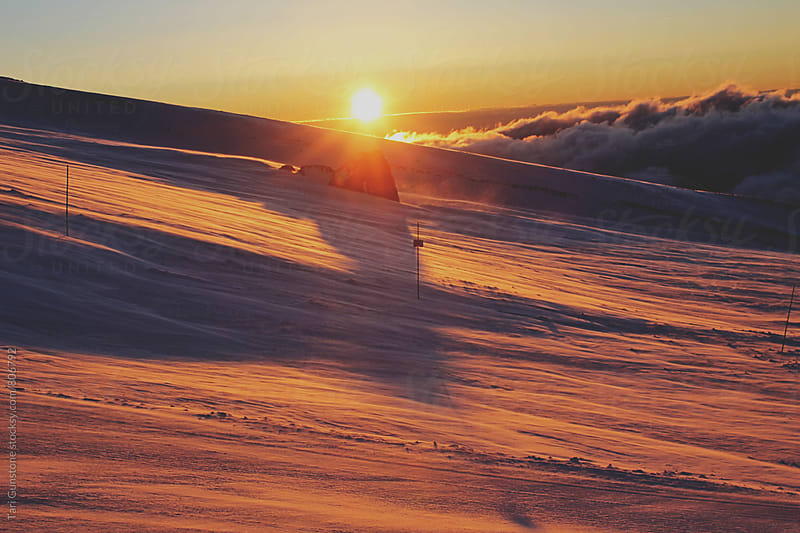 Sunrise on snowy mountain by Tari Gunstone for Stocksy United