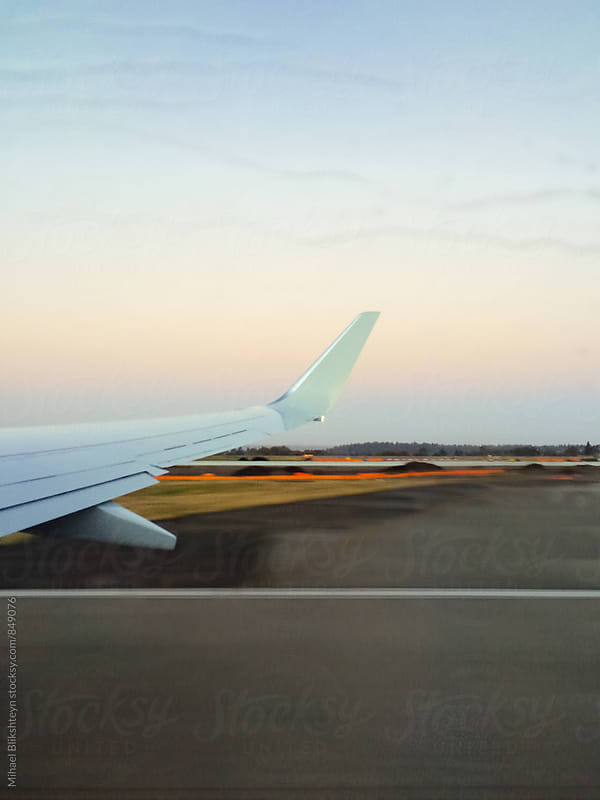 View of an airplane wing and rain on the window and tarmac by Mihael Blikshteyn for Stocksy United