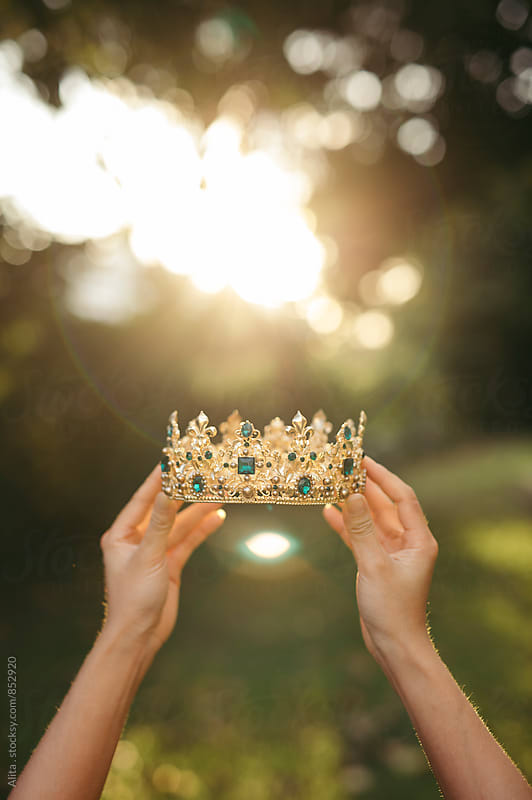 Woman's hands holding gold tiara by Alita Ong for Stocksy United