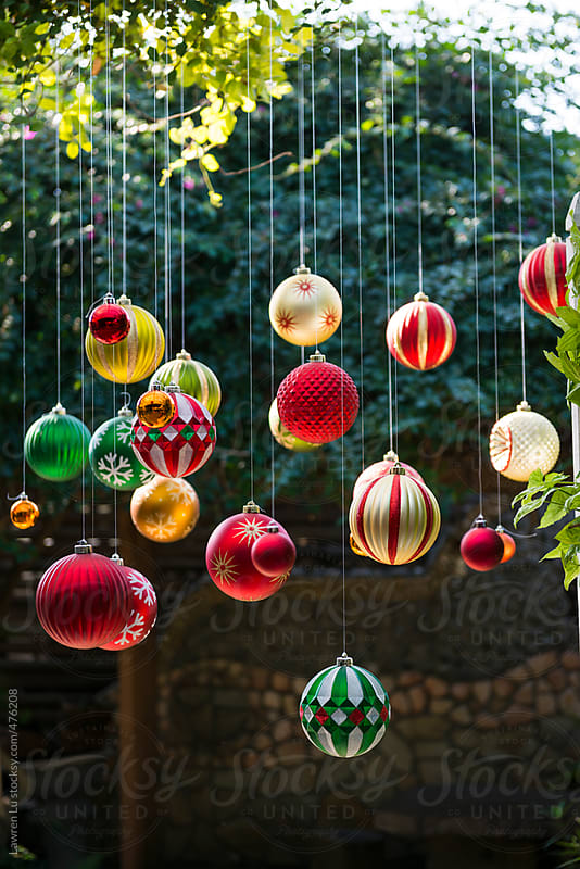 Many colorful Christmas balls hanging in the garden with sunlight by Lawren Lu for Stocksy United
