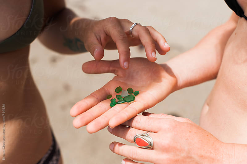 Two Young Women Looking at a Hand Full of Sea Glass by Briana Morrison for Stocksy United