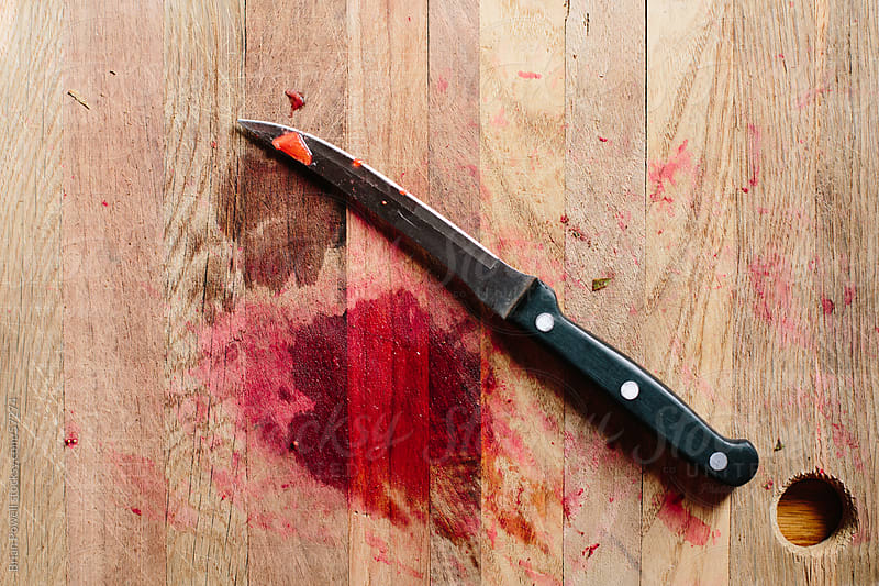 knife and stain on cutting board by Brian Powell for Stocksy United