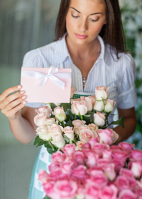 Florist arranging bouquet of roses in her shop. by Mosuno for Stocksy United