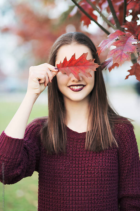 Autumn portrait of a beautiful young woman covering her eyes with a leaf by Jovana Rikalo for Stocksy United